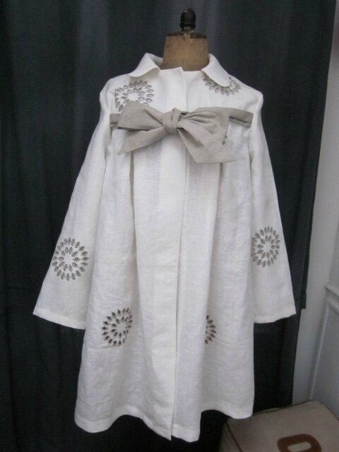 Un manteau AGLAE en lin écru ajouré et brodé de beige fermé par un noeud de lin brut...