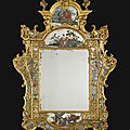 An italian carved giltwood and reverse painting on glass mirror, venetian, second quarter 18th century
