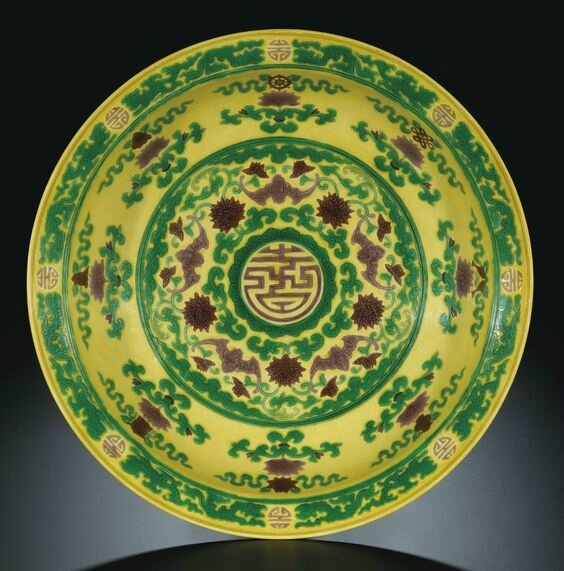 A fine large yellow and green 'Eight Buddhist Emblems' dish, seal mark and period of Qianlong (1736-1795)