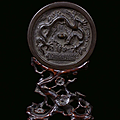 A silver plated bronze mirror with carved wood base, China, Ming Dynasty, 16th century