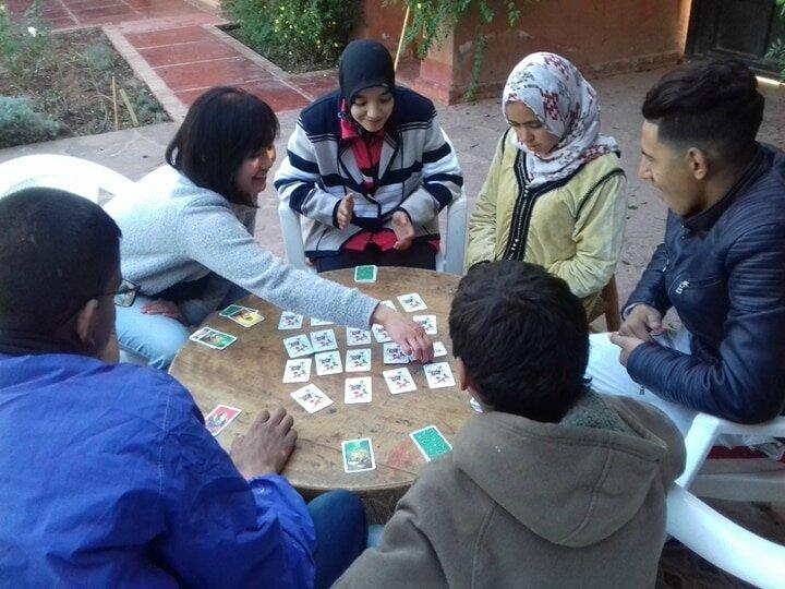 Eli avec les jeunes dans un jeu de cartes à retourner pour trouver les paires (mémory)