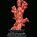 A rare red coral group representing guanyin with musicians finely sculpted, china, qing dynasty, beginning 20th century