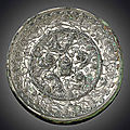 A silvery bronze 'Lion and grapevine' circular mirror, Tang dynasty (618-907)