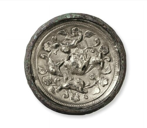 A miniature silver sheet-inlaid bronze circular mirror, China, Tang dynasty (AD 618-907)