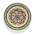 An iznik polychrome pottery dish with a stylised stellar floral motif, turkey, circa 1580-90