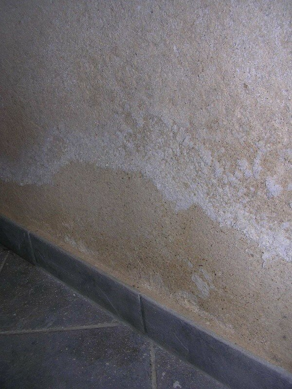 Traces de salpêtre (dues aux sels minéraux contenus dans l'eau qui migre à l'intérieur du mur)