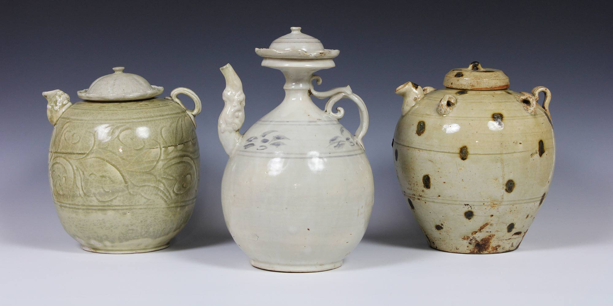 Ewers with lids, stoneware with incised design and celadon glaze, height 20 cm, stoneware with cream and iron underglaze, height 21 cm, stoneware with pale olive-green glaze and iron brown splotches, height 21 cm, Tran dynasty (1225-1400), Vietnam