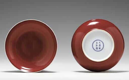 A pair of copper-red-glazed saucer dishes, Yongzheng six-character marks in underglaze blue within a double circle and of the period (1723-1735)