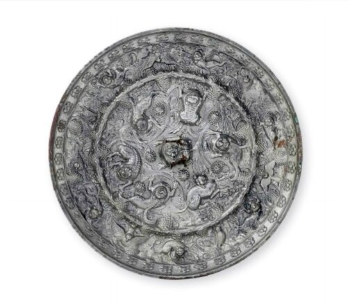 A large silvery bronze 'Lion and grapevine' circular mirror, China, Tang dynasty (AD 618-907)