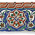 An iznik polychrome pottery border tile with composite flowerhead and key fret red border, turkey, circa 1550-1600