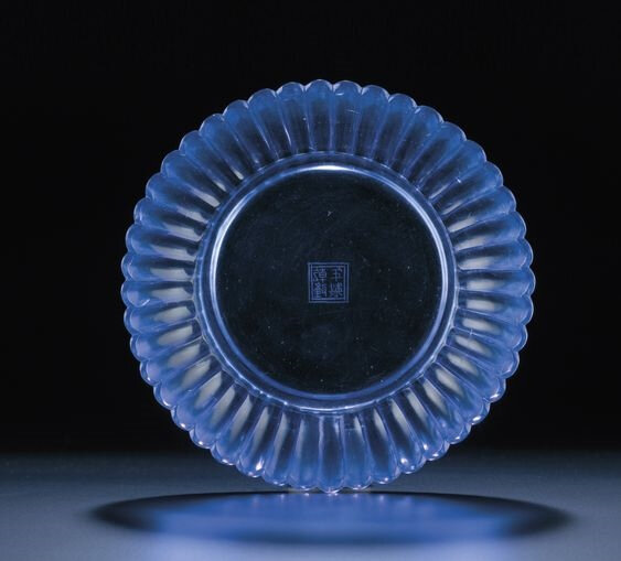 A very rare imperial transparent blue glass 'chrysanthemum' dish, Qianlong incised four-character mark within double-squares and of the period (1736-1795)