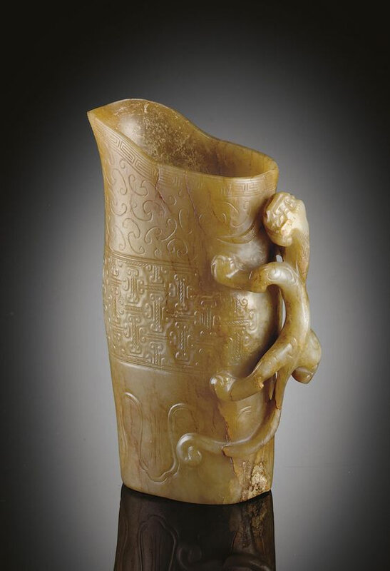 A well-carved greenish-white and pale brown jade rhyton, Song-Ming dynasty, 12th-16th century