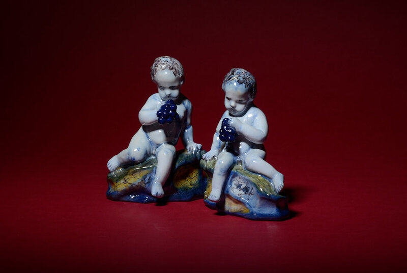 Pair of Polychrome Figures of Seated Putti with Grapes, Delft, circa 1760