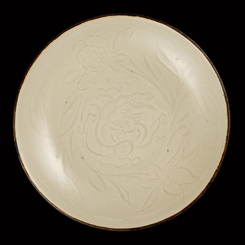 A rare carved Dingyao 'chilong' dish, Song dynasty (960-1279)