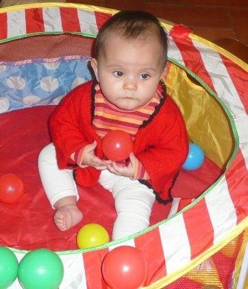 amélia ds son parc avec gilet rouge gros plan