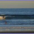Surfeurs, voilier et bâteau de pêche