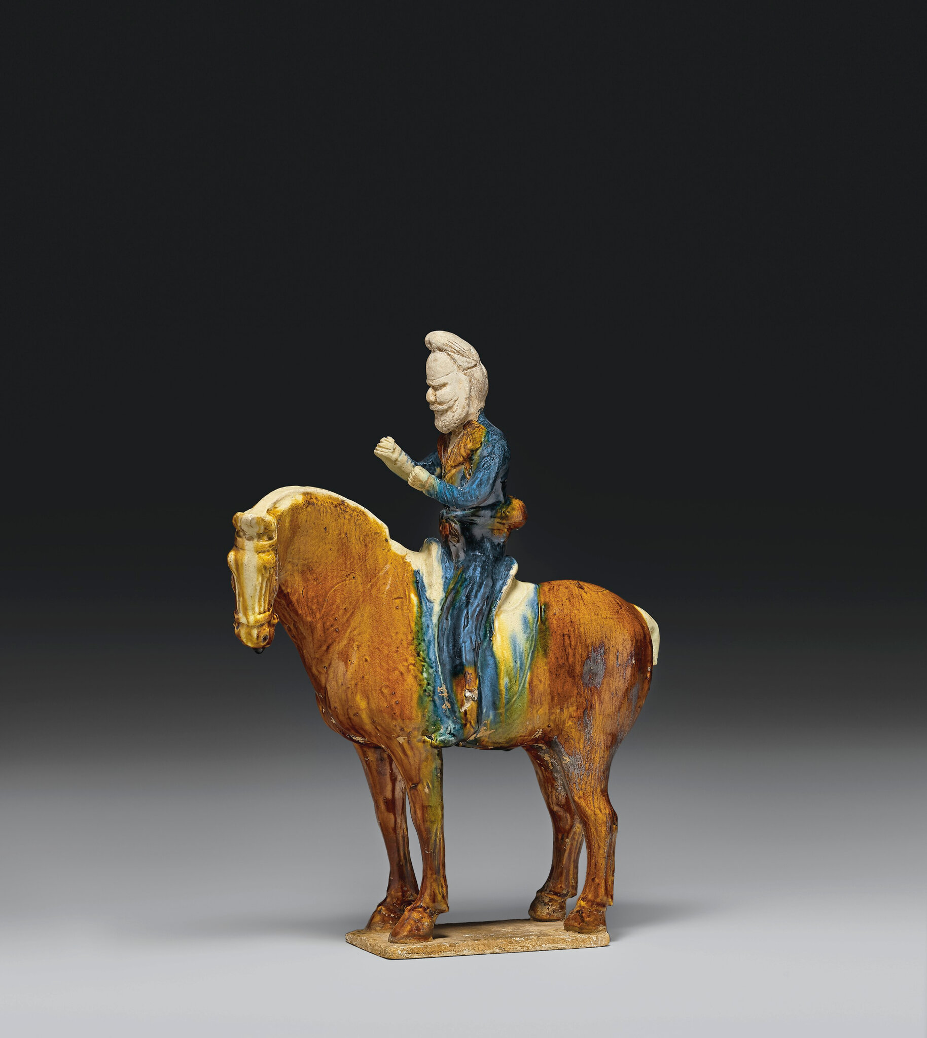 A rare blue and sancai-glazed pottery figure of an equestrian, Tang dynasty (618-907)