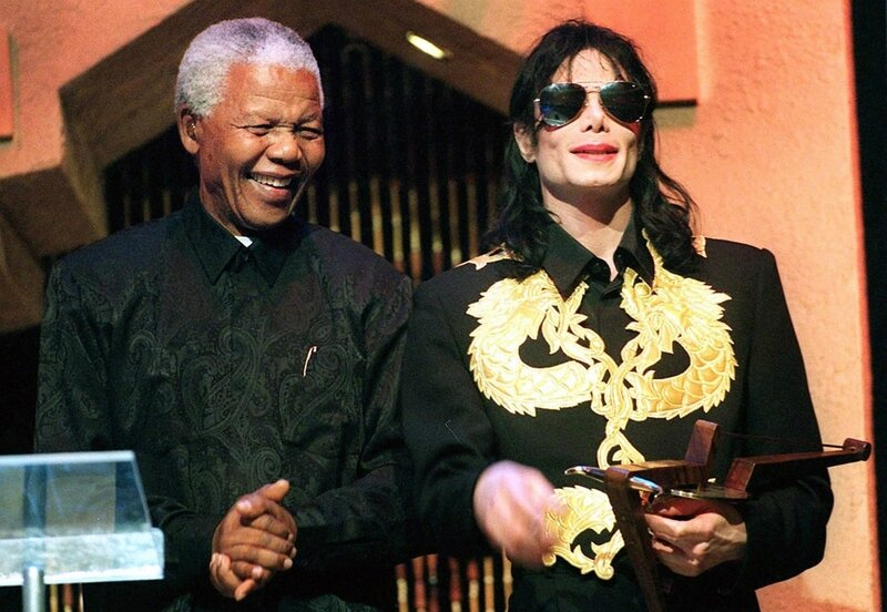 6059403-Former-South-African-President-Nelson-Mandela-claps-his-hands-after-American-