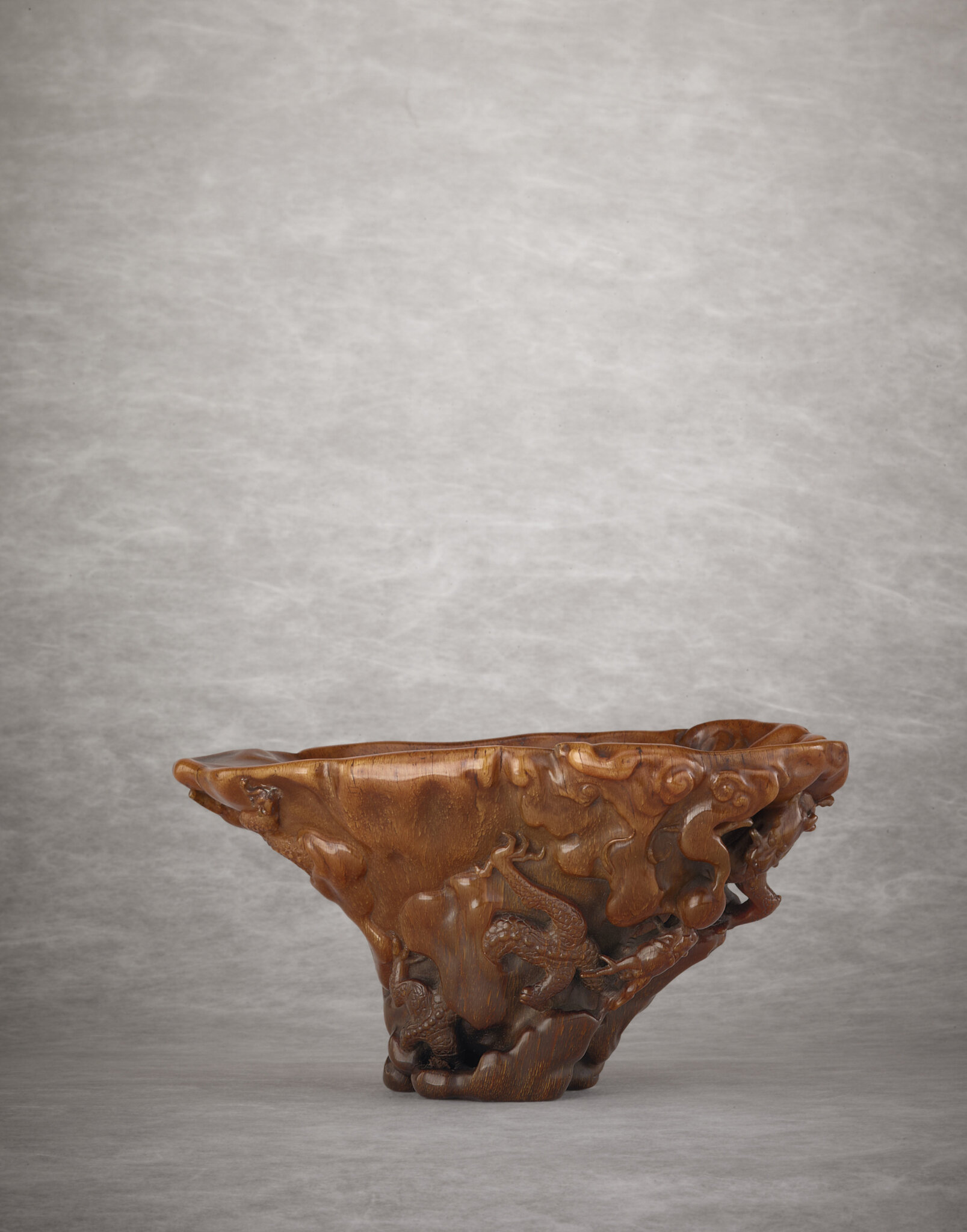 A rare and superbly carved rhinoceros horn 'dragon' libation cup, Qing dynasty, early 18th century