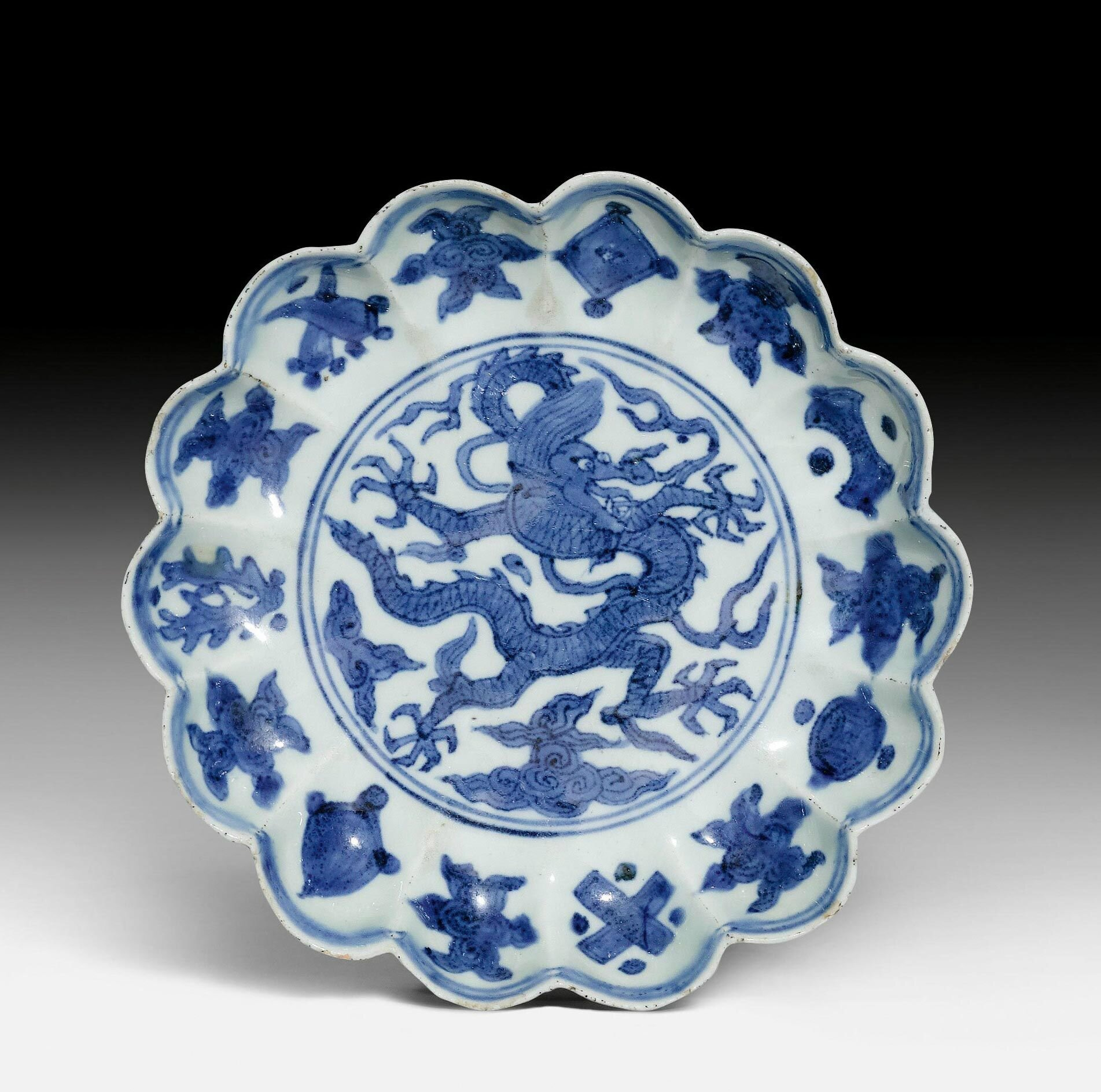 A very rare blue and white lobed saucer dish painted with an Imperial dragon and Daoist symbols, Longqing mark and of the period (1567-1572)